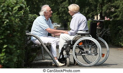Disabled spouse - Retired couple spending time outdoors,...