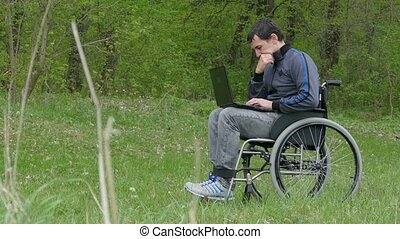disabled thinks problems man wheelchair with laptop in wheelchair working on nature green background