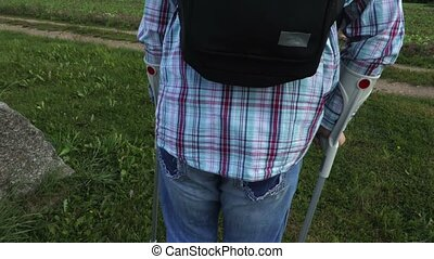 Disabled traveler with crutches and backpack