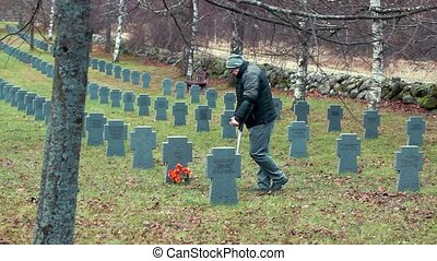Disabled veteran near to the tomb monument with flowers in...
