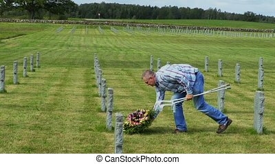 Disabled veteran put flower wreath on the grave