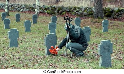 Disabled veteran with crutches in graveyard.