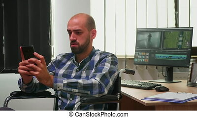Disabled photo designer sitting in wheelchair searching on internet using smartphone texting, networking. Immobilized videographer editing new project working in modern company creating content
