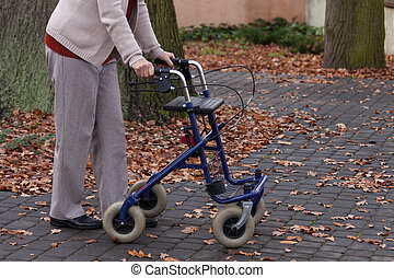 Disabled person walking with walker outdoors, horizontal