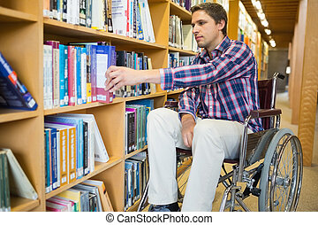 Disabled wheelchair selecting book in library - Man in...