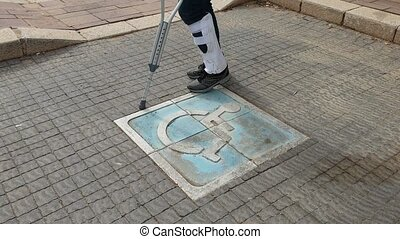 Disabled with crutches and plaster cross disabled parking slot shot clip