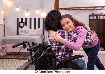Disabled woman and jolly girl sharing love