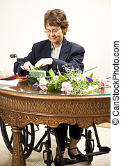 Disabled Woman Arranges Flowers - Mature woman in wheelchair...