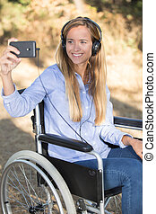 disabled woman in the wheelchair taking a selfie