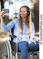 disabled woman in the wheelchair taking selfie