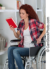 disabled woman in wheelchair reading book