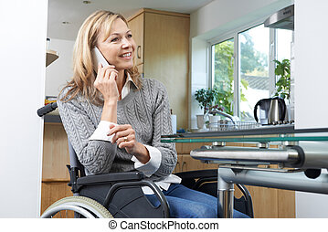 Disabled Woman In Wheelchair Talking On Mobile Phone At Home