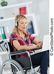 disabled woman in wheelchair using laptop to listen to music
