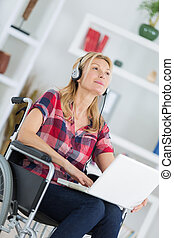 disabled woman in wheelchair with laptop and headphones