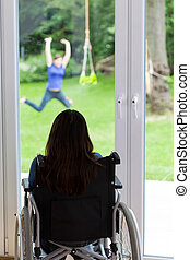 Disabled woman looking at healthy girl