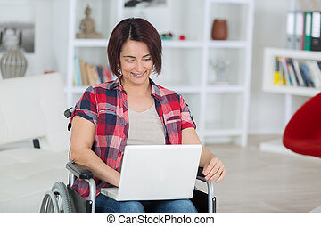 disabled woman on wheelchair with laptop at home