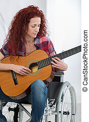 disabled woman playing guitar in her living room