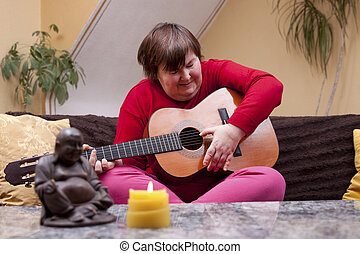 Disabled woman plays guitar and is happy