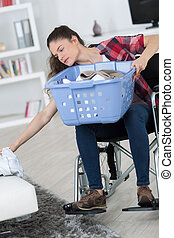 disabled woman reaching for the clothes on the sofa