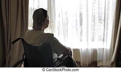 Disabled woman sit on wheelchair and looks through the window
