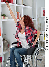 disabled woman struggling to reach a book on a shelf