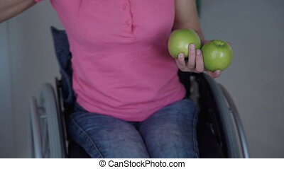 Disabled woman taking apple and put on table sitting on...