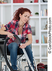 disabled woman using a vacuum cleaner at home