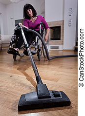 Disabled woman using vacuum cleaner