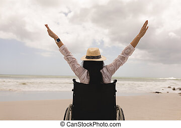 Disabled woman with arms stretched out sitting on wheelchair at beach