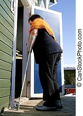 Disabled woman with crutch entering her shabby old home