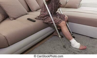 Disabled woman with crutches on couch try to stand up
