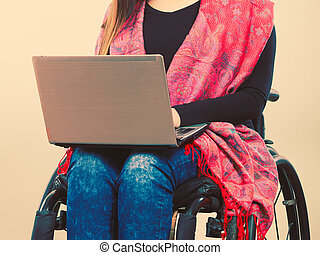 Disabled woman with laptop on wheelchair.