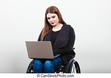 Disabled woman with laptop on wheelchair. - Technology and...