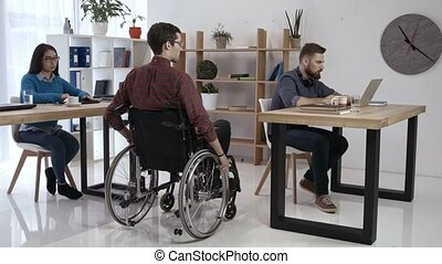 Disabled worker and colleagues working in office - Disabled...