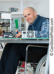 disabled worker in wheelchair fixing a computer