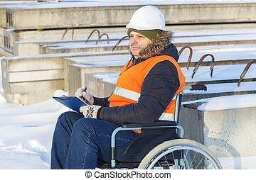 Disabled worker on wheelchair writing in construction site