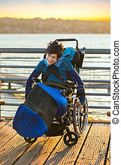 Disabled young boy in wheelchair by lake at sunset