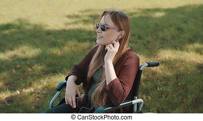 Disabled young caucasian woman listening the music in the park in the wheelchair. High quality 4k footage