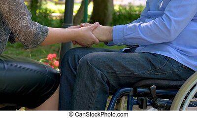 Disabled young man encouraged by his wife outdoors
