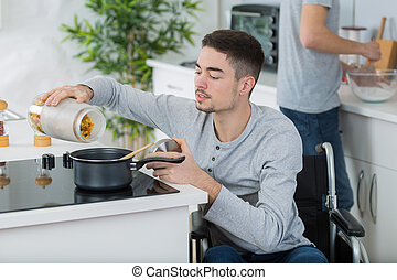 disabled young man in wheelchair cooking a meal in kitchen