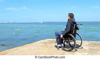 Disabled young man sitting in a wheelchair and looks at the...