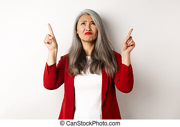 Disappointed asian senior woman looking, pointing fingers up and grimacing, dislike something, standing skeptical over white background