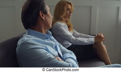 Disappointed couple sitting in psychologists office - Saving...