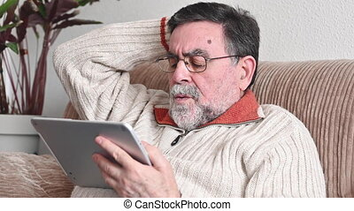 Disappointed Elder man Read Bad News on Tablet Screen and Gesticulates Upset. High quality 4k footage