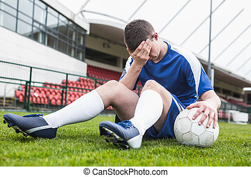 Disappointed football player in blue sitting on pitch after...