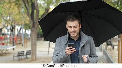 Disappointed man receiving wrong phone message in a rainy...