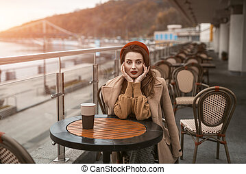 Disappointed or frustrated french young woman sitting outdoors restaurant terrace with coffee mug female fashion. Portrait of stylish young woman wearing autumn coat and red beret outdoors.