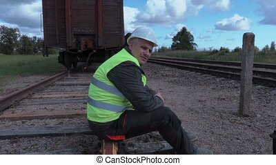 Disappointed rail worker with tablet sitting on rails