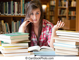 Disappointed student having a lot to read in a library