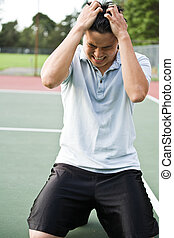 Disappointed tennis player - An asian tennis player...